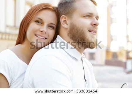 Close up portrait of a happy couple sitting on a scooter. Handsome bearded young man looking ahead and a red-haired pretty girl smiling while looking at the camera - stock photo