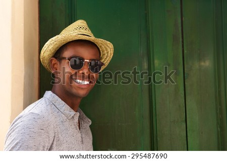 Close up portrait of a happy guy with hat and sunglasses  - stock photo