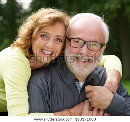 Close up portrait of a happy husband and wife smiling outdoors - stock photo