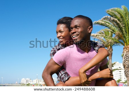 Close up portrait of a happy man carrying girlfriend outdoors - stock photo