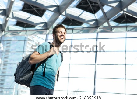 Close up portrait of a happy man traveling with bag in airport - stock photo