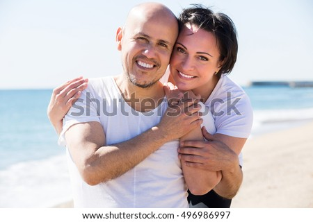 Close-up portrait of a happy mature man and a woman happily embracing each other on the beach