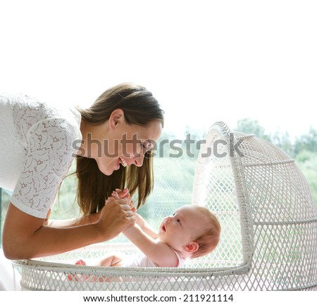 Close up portrait of a happy mother and cute baby playing - stock photo