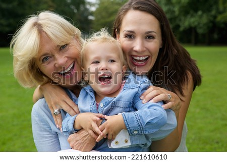 Close up portrait of a happy mother granddaughter and baby smiling outdoors - stock photo