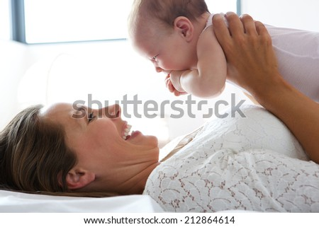 Close up portrait of a happy mother holding cute baby in bed - stock photo