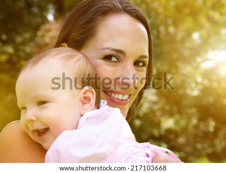 Close up portrait of a happy mother holding smiling baby - stock photo