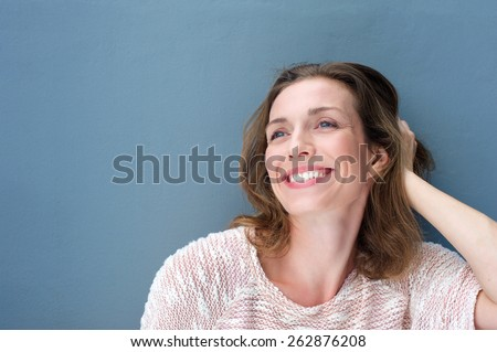 Close up portrait of a happy older woman laughing with hand in hair - stock photo