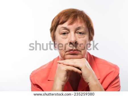 Close up portrait of a happy smiling senior woman resting her chin on her hands and looking directly at the camera - stock photo