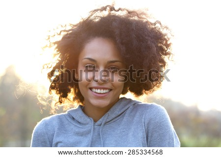 Close up portrait of a happy smiling young woman with curly hair - stock photo