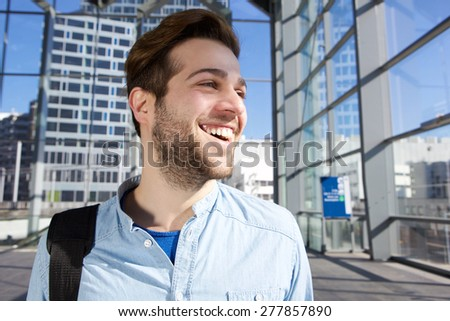 Close up portrait of a happy traveling man smiling at station - stock photo