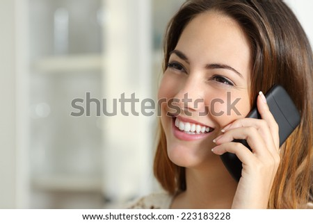 Close up portrait of a happy woman talking on the mobile phone at home - stock photo