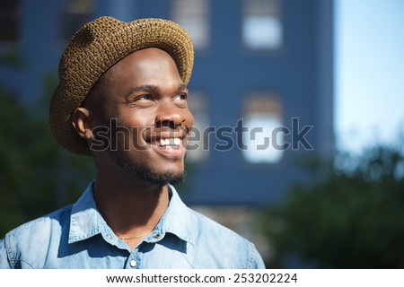 Close up portrait of a happy young african american man smiling outdoors with hat - stock photo