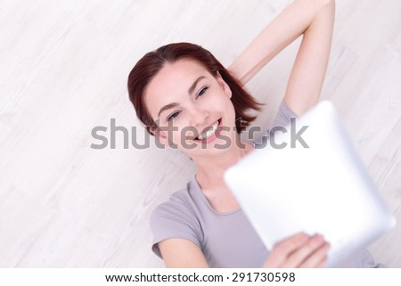 Close up portrait of a Happy young beautiful woman relax lying and use tablet pc, caucasian beauty - stock photo