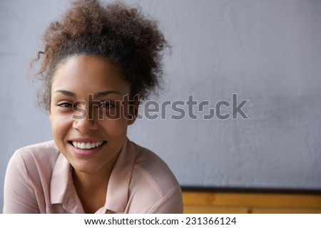 Close up portrait of a happy young black woman smiling  - stock photo