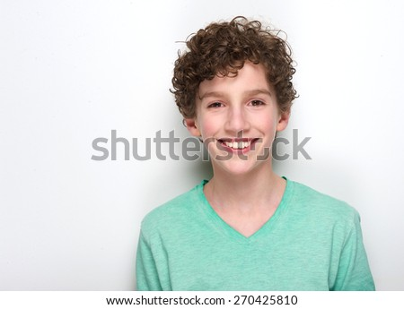 Close up portrait of a happy young boy with curly hair smiling against white background - stock photo
