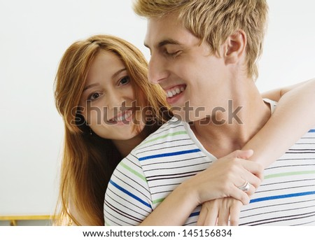 Close up portrait of a happy young couple hugging indoors and smiling, having fun together. - stock photo