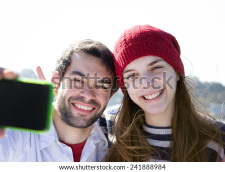 Close up portrait of a happy young couple smiling and taking selfie with mobile phone - stock photo