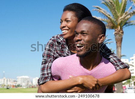 Close up portrait of a happy young man carrying attractive girlfriend on his back - stock photo