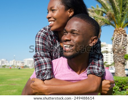 Close up portrait of a happy young man carrying girlfriend on back  - stock photo