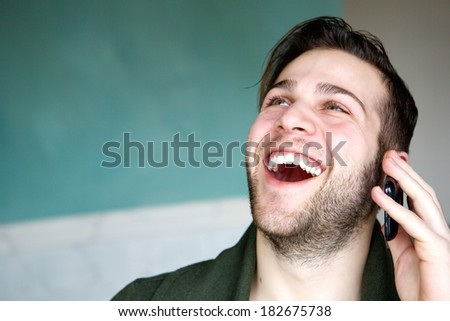 Close up portrait of a happy young man laughing while using mobile phone at home
