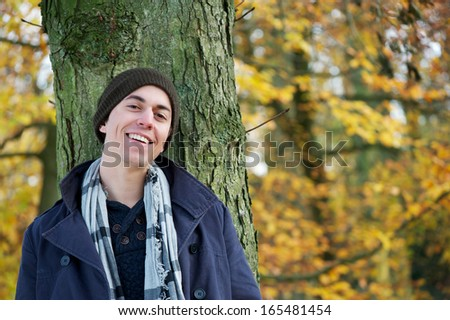 Close up portrait of a happy young man smiling outdoors - stock photo
