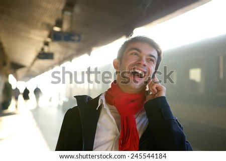 Close up portrait of a happy young man talking on mobile phone at train station - stock photo
