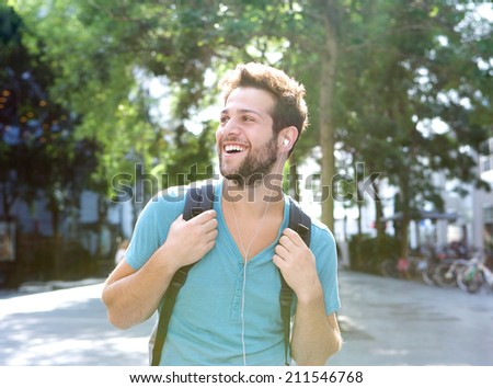 Close up portrait of a happy young man traveling with backpack and earphones  - stock photo