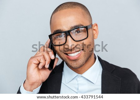 Close-up portrait of a happy young man wearing eyeglasses talking on cell phone isolated on gray background