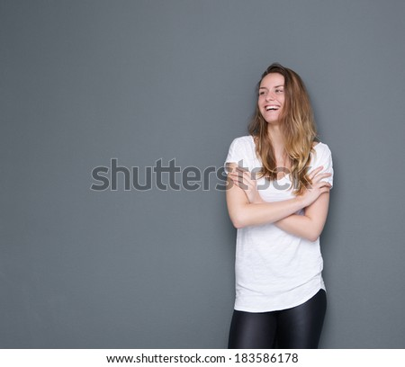 Close up portrait of a happy young woman laughing with arms crossed on gray background - stock photo