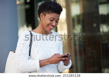 Close up portrait of a happy young woman walking in the city sending text message on cellphone - stock photo