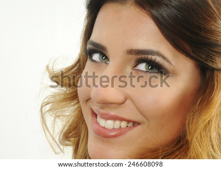 close up portrait of a head shot of a Young caucasian girl with a beautiful smile and Young clean skin showing her perfect White teeth and an evening make up isolated on white  - stock photo