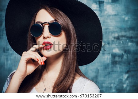 Close-up portrait of a hipster girl wearing hat and round sunglasses. Beauty, cosmetics.