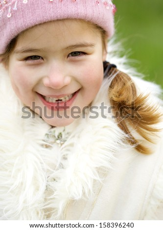 Close up portrait of a joyful beautiful young child girl standing in a green park smiling happy during a cold winter day, wearing a warm coat and a pink hat, outdoors. - stock photo