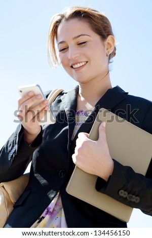 Close up portrait of a joyful businesswoman using her smartphone and carrying work folders, standing against a sunny blue sky. - stock photo