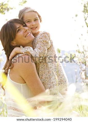 Close up portrait of a joyful mother and daughter relaxing together in a beautiful spring field of grass and flowers, hugging and enjoying a sunny holiday outdoors. Family love active lifestyle. - stock photo