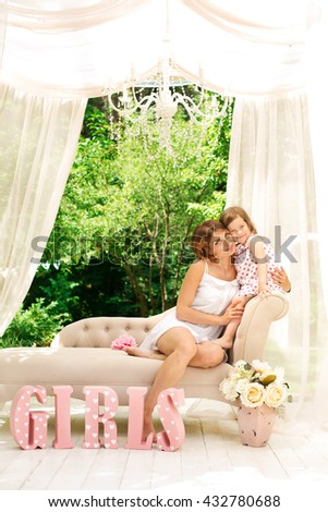 Close up portrait of a joyful mother and daughter relaxing together in a beautiful spring field of grass and flowers, hugging and enjoying a sunny holiday outdoors. Family love and lifestyle.