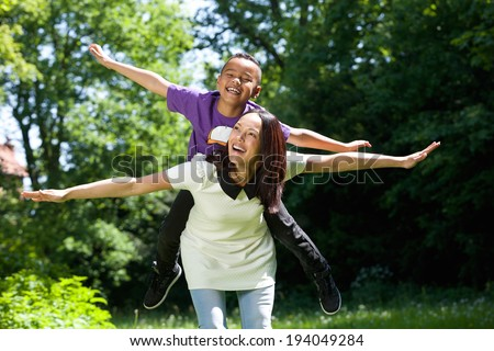 Close up portrait of a joyful mother and son with arms spread pretending to fly - stock photo