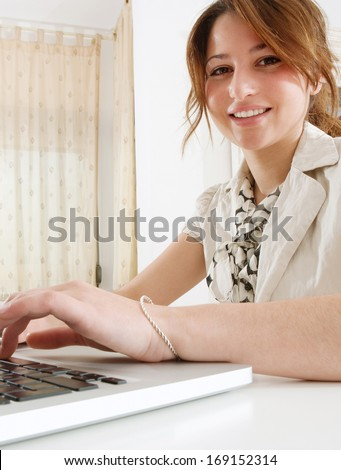 Close up portrait of a joyful professional business woman using a laptop computer at her working desk, typing while sitting at her white home office and smiling at the camera. Office interior. - stock photo