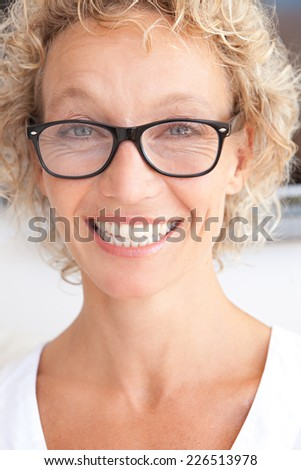 Close up portrait of a joyful professional successful woman smiling at the camera in an office interior. Business woman wearing reading glasses and with a cheerful face expression, indoors. - stock photo