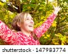 Close up portrait of a joyful teenage girl standing in a forest during the autumn season, surrounded by changing color leaves and trees with her arms outstretched up, outdoors. - stock photo