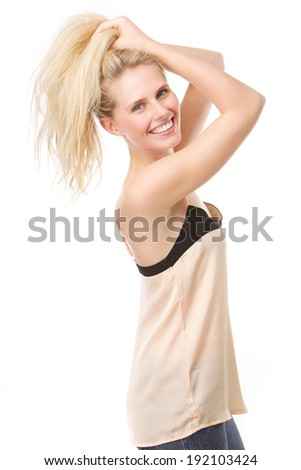 Close up portrait of a joyful young woman with hands in hair posing on isolated white background