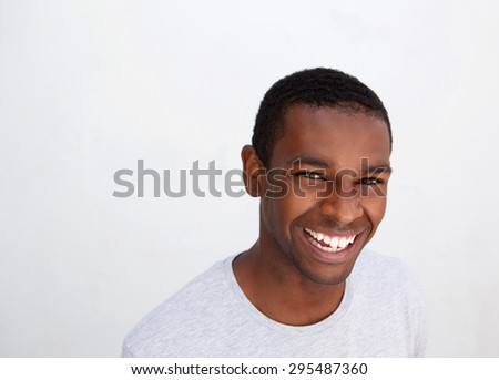 Close up portrait of a laughing black guy posing against white background - stock photo