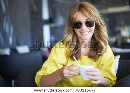 Close-up portrait of a laughing middle aged woman sitting at cafe and drinking morning coffee.