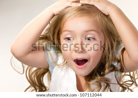 close-up portrait of a little amazing  girl with opening mouth looking  down - stock photo