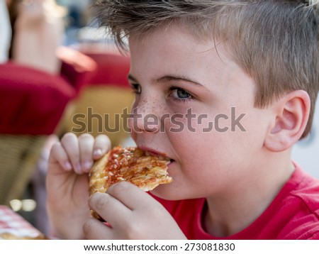 close up portrait of a little boy eating a pizza slice - stock photo
