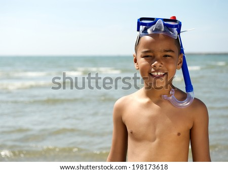 Close up portrait of a little boy smiling with snorkel at the beach - stock photo