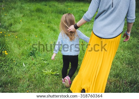close-up portrait of a little girl child with blond hair walking in the park with her mother in a yellow skirt posing and smiling - stock photo