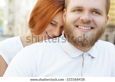 Close up portrait of a lovely couple. Handsome bearded young man smiling looking aside, while his red-haired girlfriend sitting behind him being a little shy - stock photo