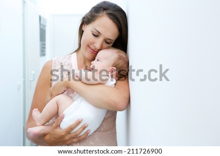 Close up portrait of a loving mother holding newborn child