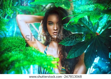 Close-up portrait of a magnificent sexy woman in bikini among tropical plants. Make-up, cosmetics. Beauty, fashion. Spa, healthcare. Tropical vacation. - stock photo